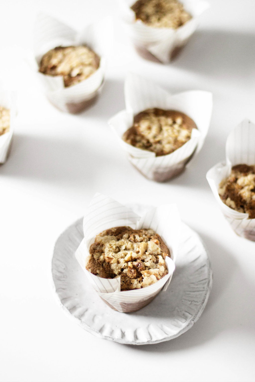 A freshly baked batch of vegan streusel muffins is lined up against a white surface. The muffins are encased in white, paper liners.