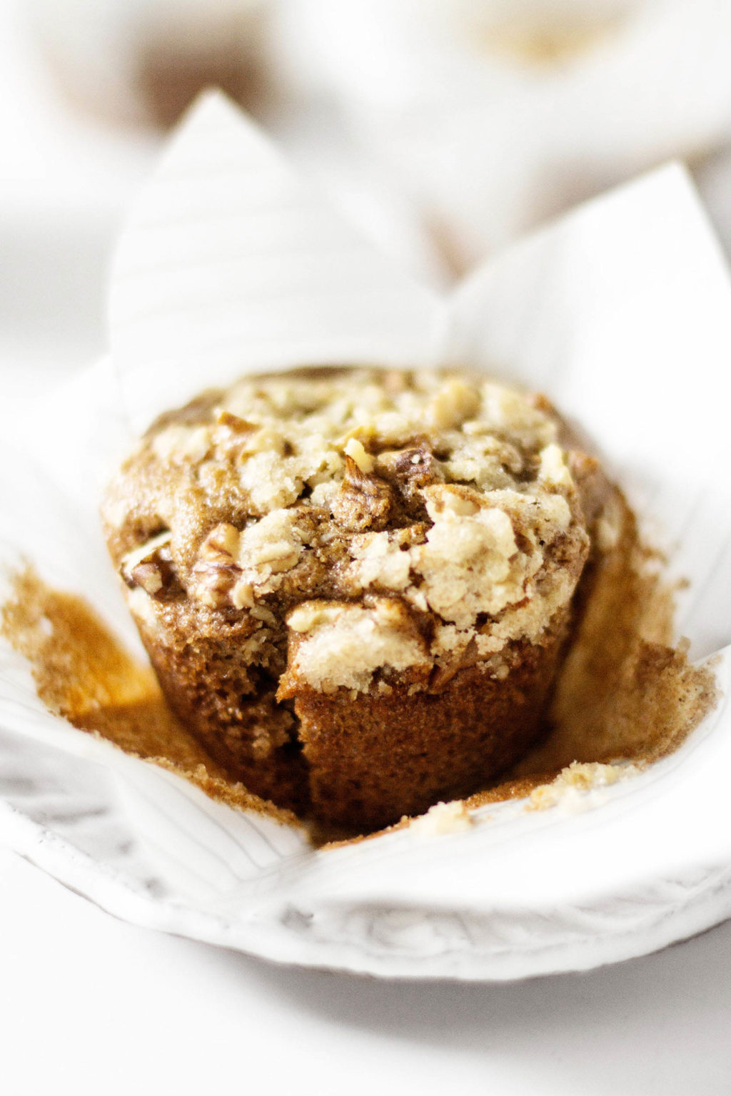 A vegan muffin is being held in a white paper liner. It rests on a white dessert plate.