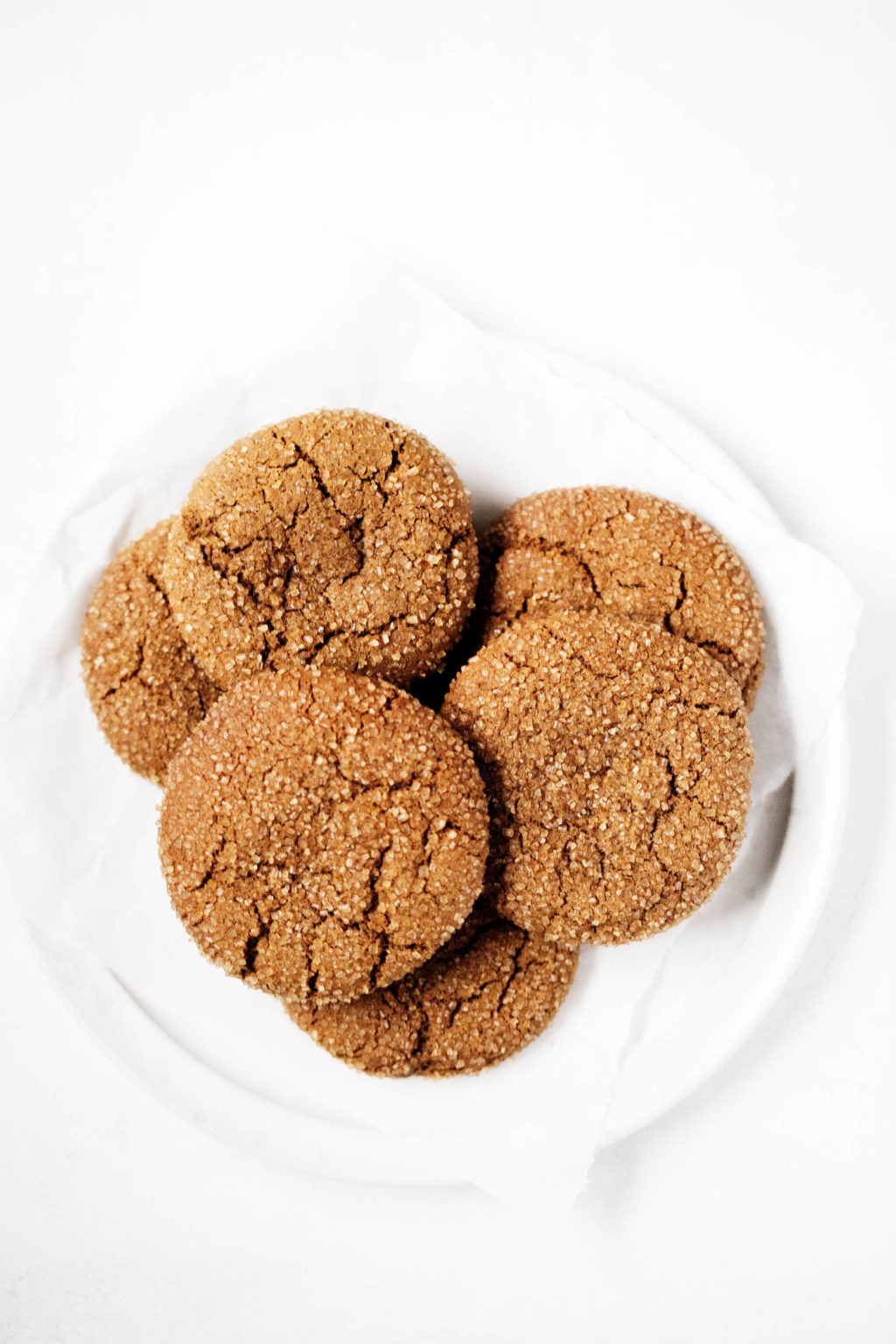 A small, round dessert plate has been piled with freshly baked holiday gingersnaps.