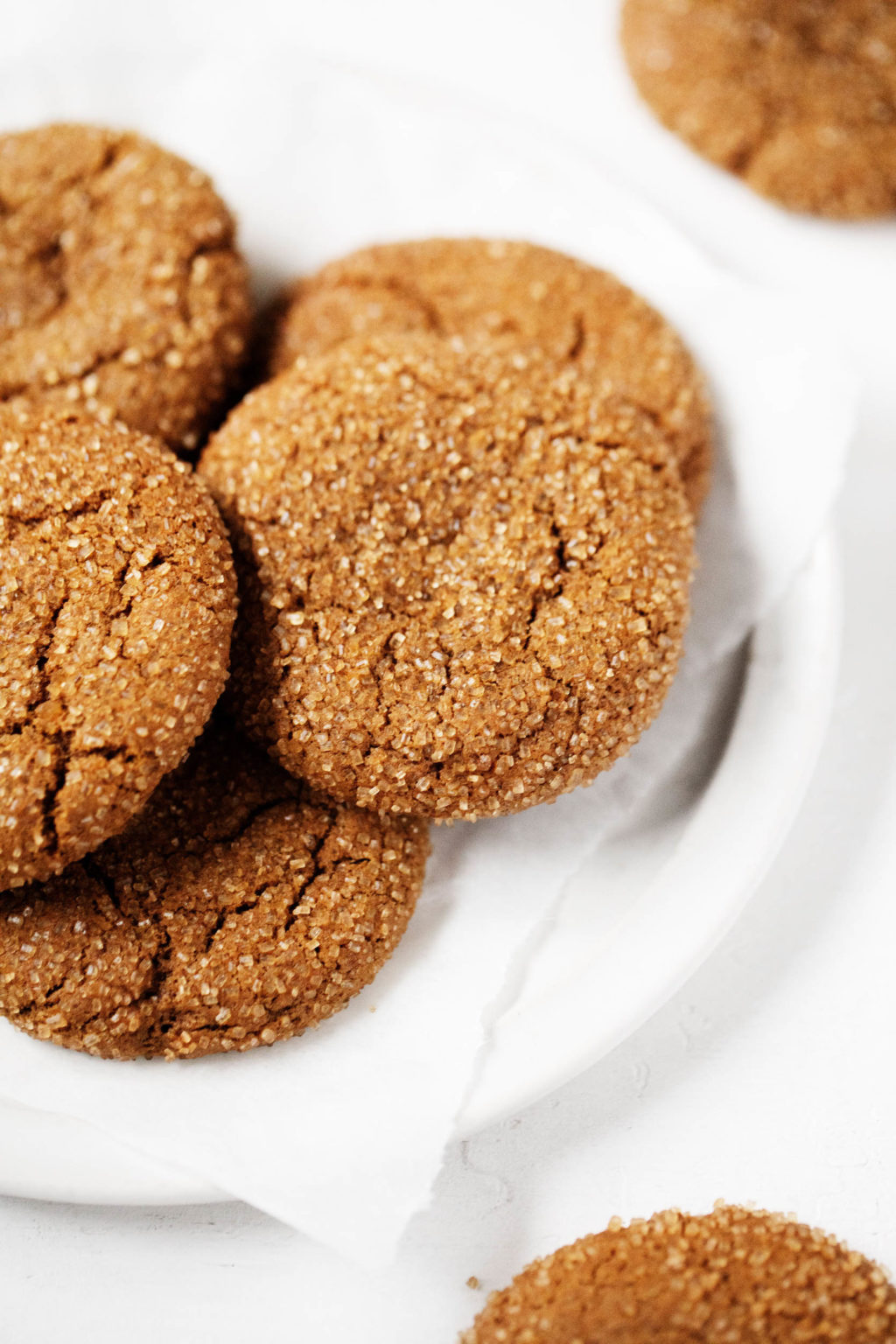 A few vegan molasses ginger cookies are piled onto a plate.