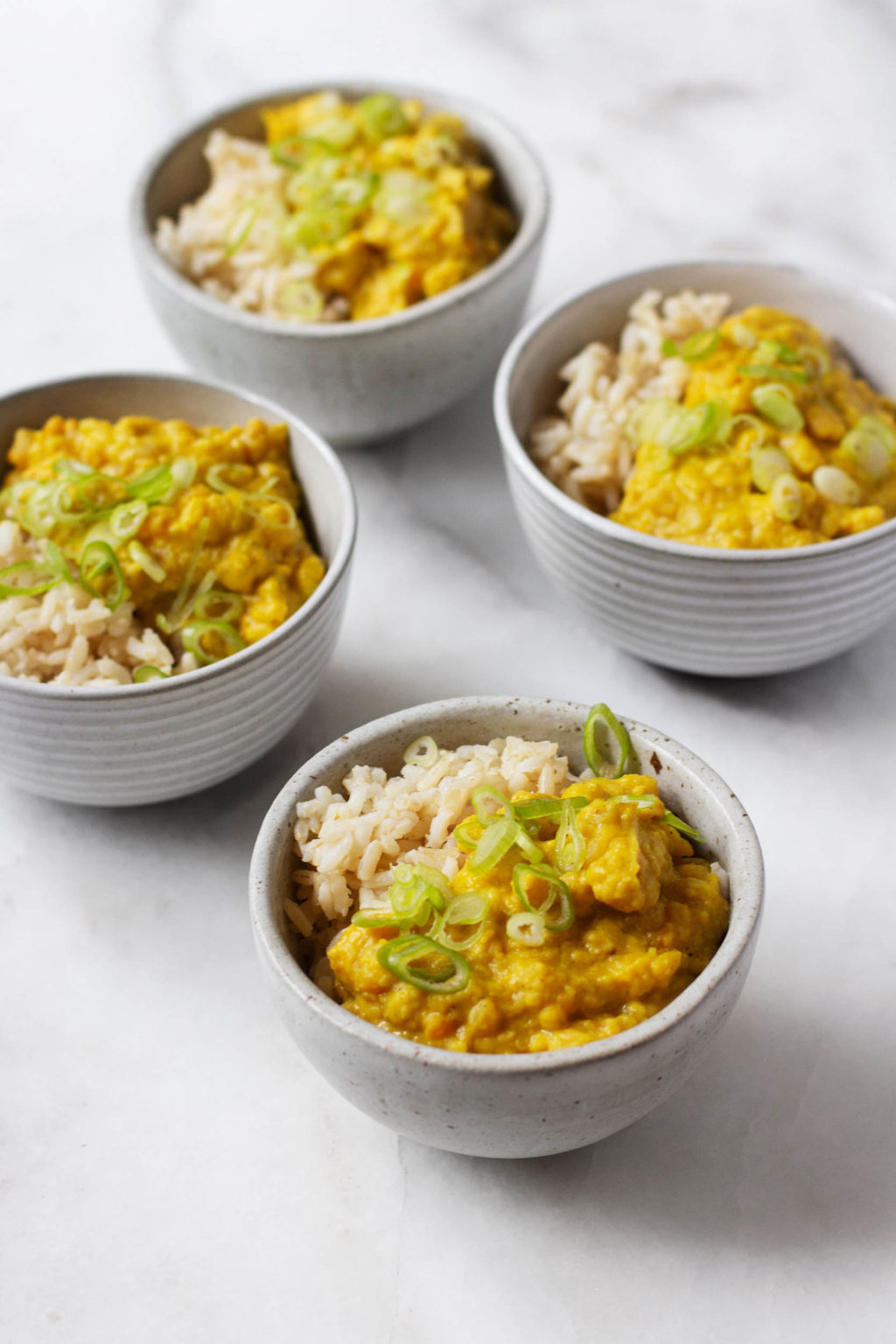 Several small bowls of a savory vegan breakfast porridge, prepared with split peas and coconut and served over rice.