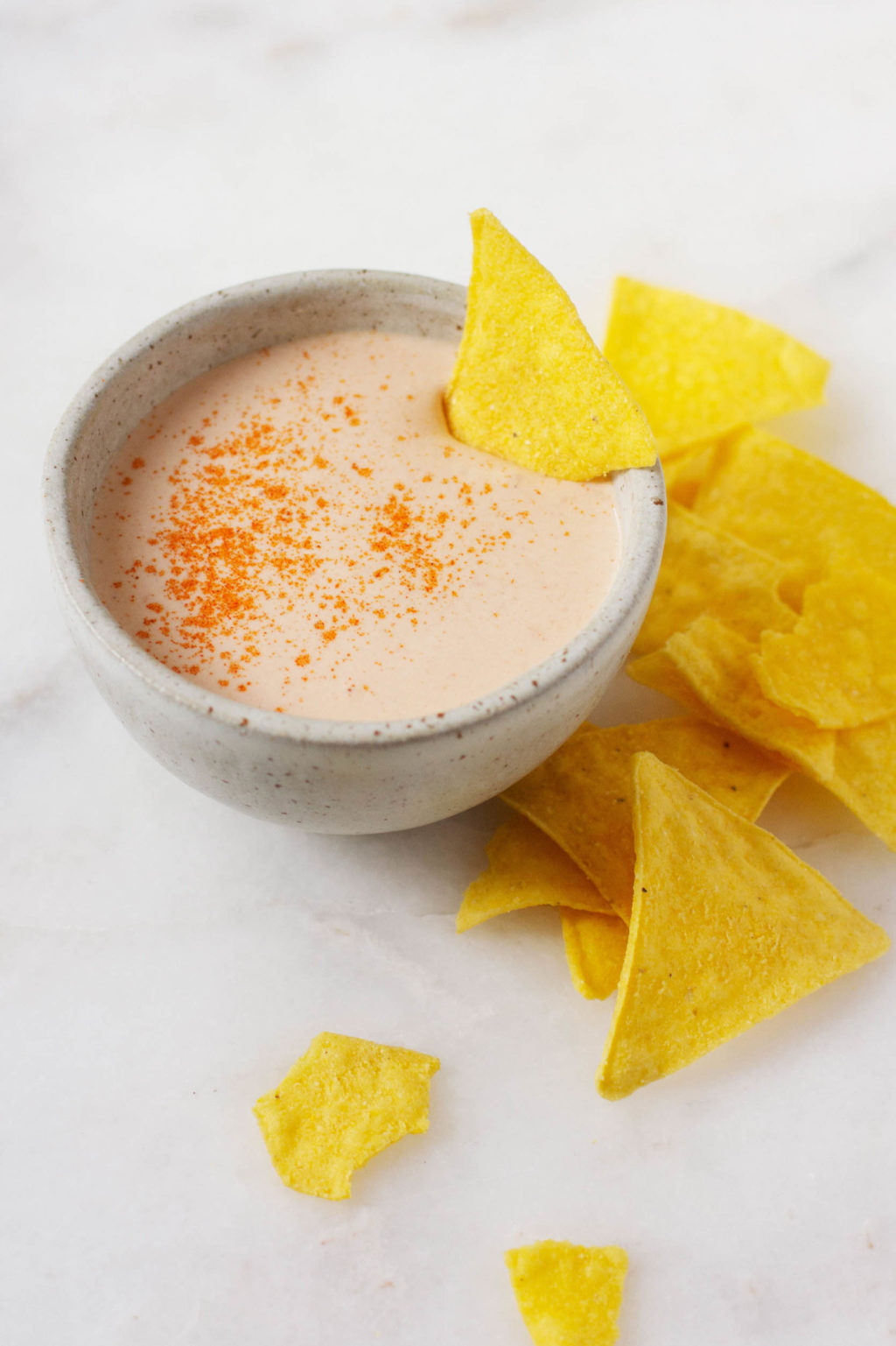 A small, circular bowl of a creamy vegan nacho sauce is accompanied by corn chips. One of the corn chips has been dipped into the sauce.