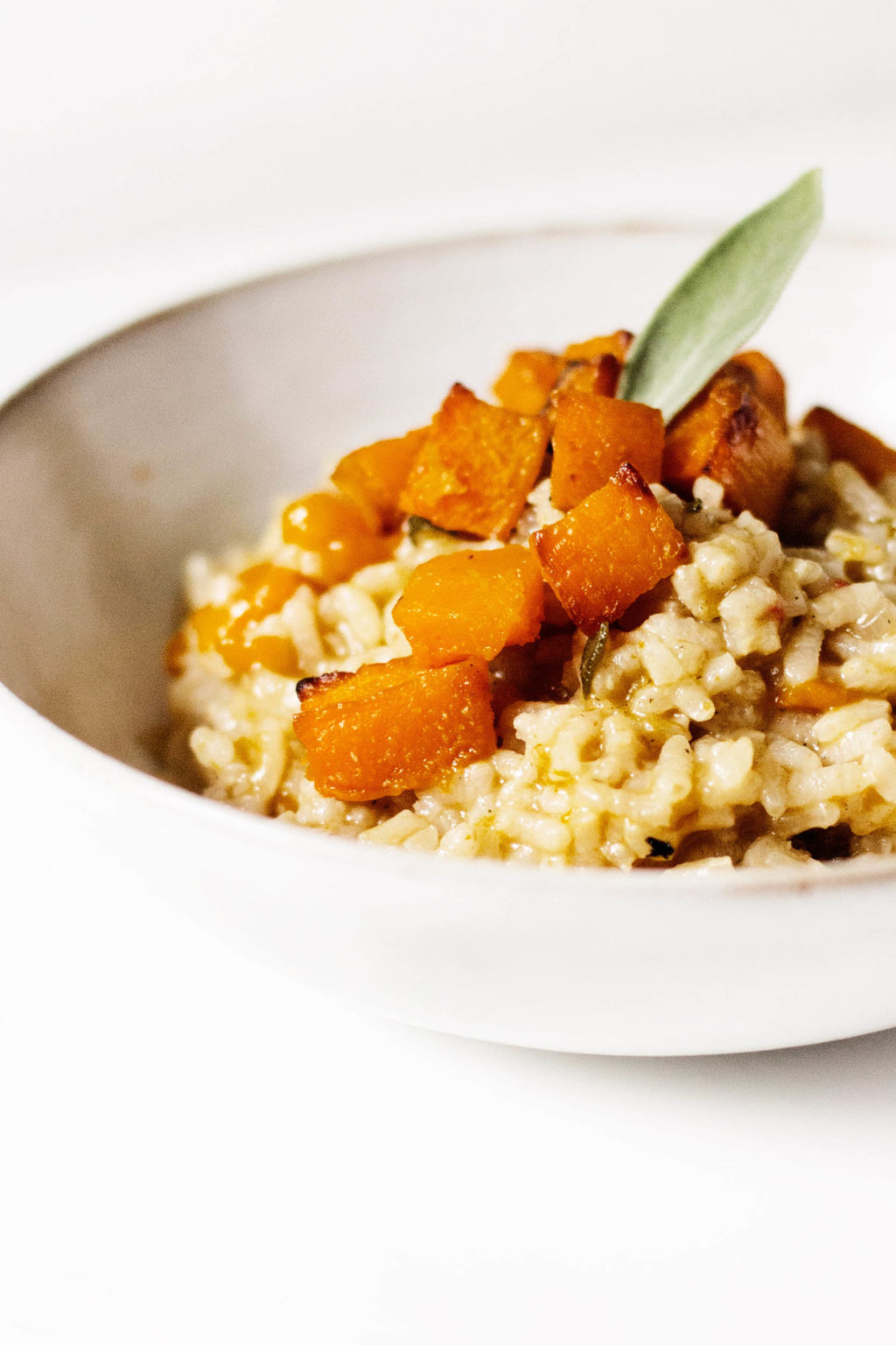 An angled shot of a vegan butternut squash risotto, garnished with sage.