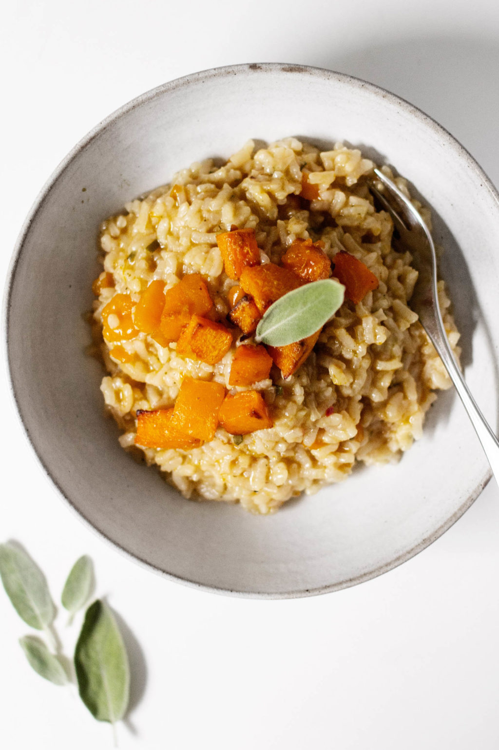 A bowl of autumn risotto with roasted butternut squash and sage leaves.