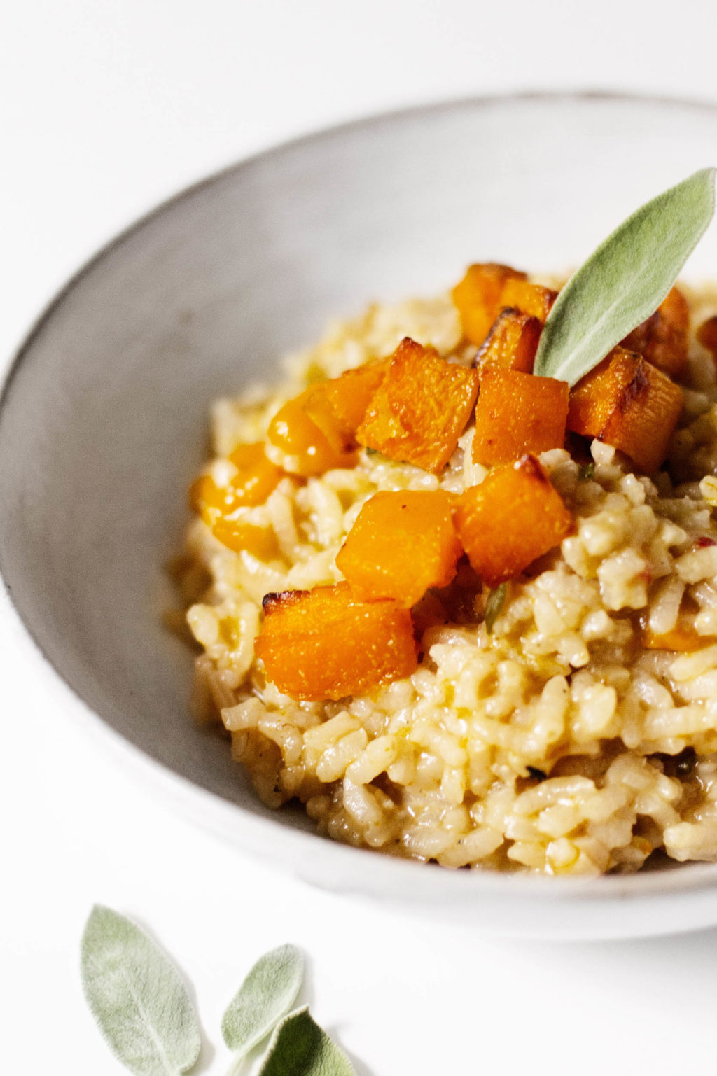 A close up photograph of a creamy vegan risotto, made with tender roasted butternut squash.
