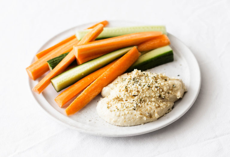 A round, white plate is covered in ingredients for a snack, including a vegan hemp hummus and raw crudites.