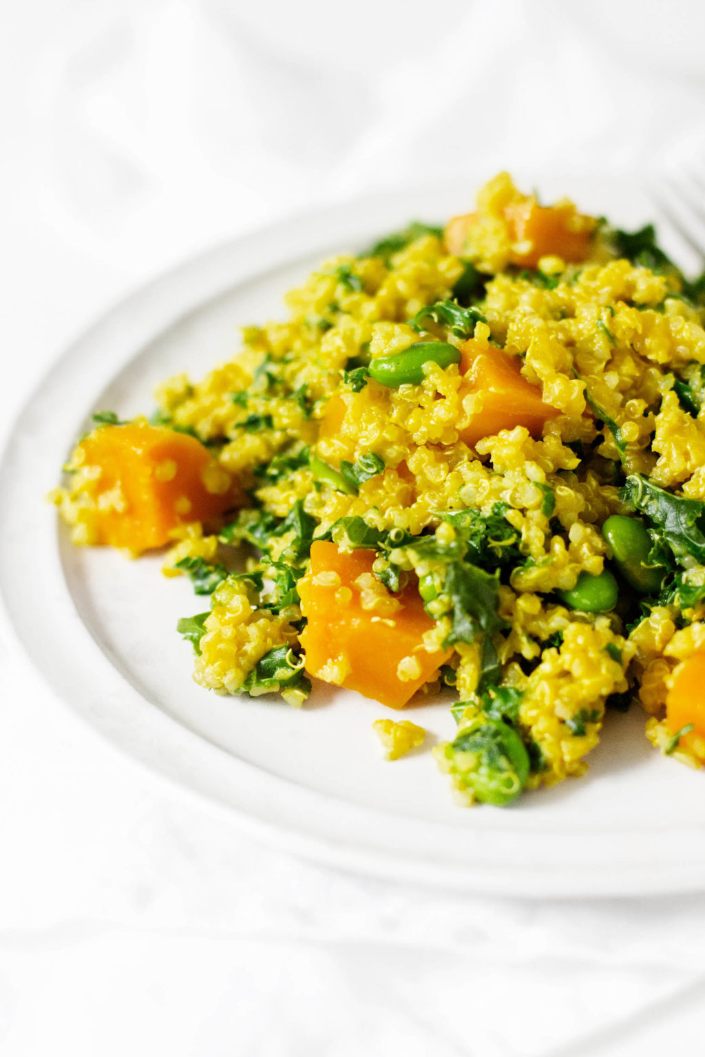 A golden colored plate of quinoa, butternut squash, edamame, and kale, brought together with a creamy sauce.