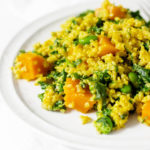 An angled photograph of a protein rich vegan meal, made with quinoa, edamame, squash, and greens.