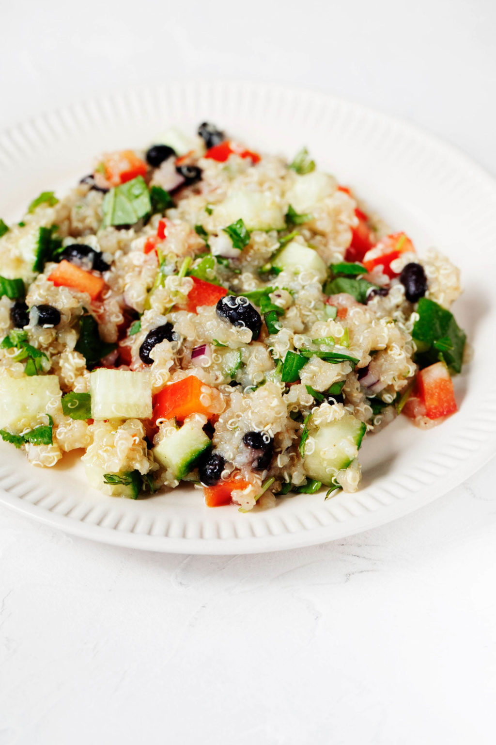An angled image of a colorful quinoa black bean salad, which has been piled onto a fluted, white ceramic plate. The plate is on a white surface.
