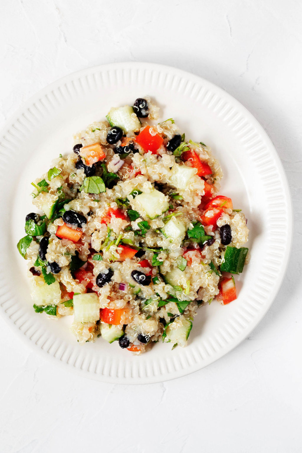 A white salad plate with a fluted rim has been piled with a plant-based grain salad. The salad is full of colorful vegetables and fresh herbs.