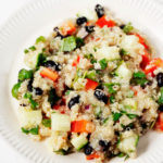 A white, fluted plate is piled with a colorful salad of quinoa, black beans, and assorted diced vegetables.