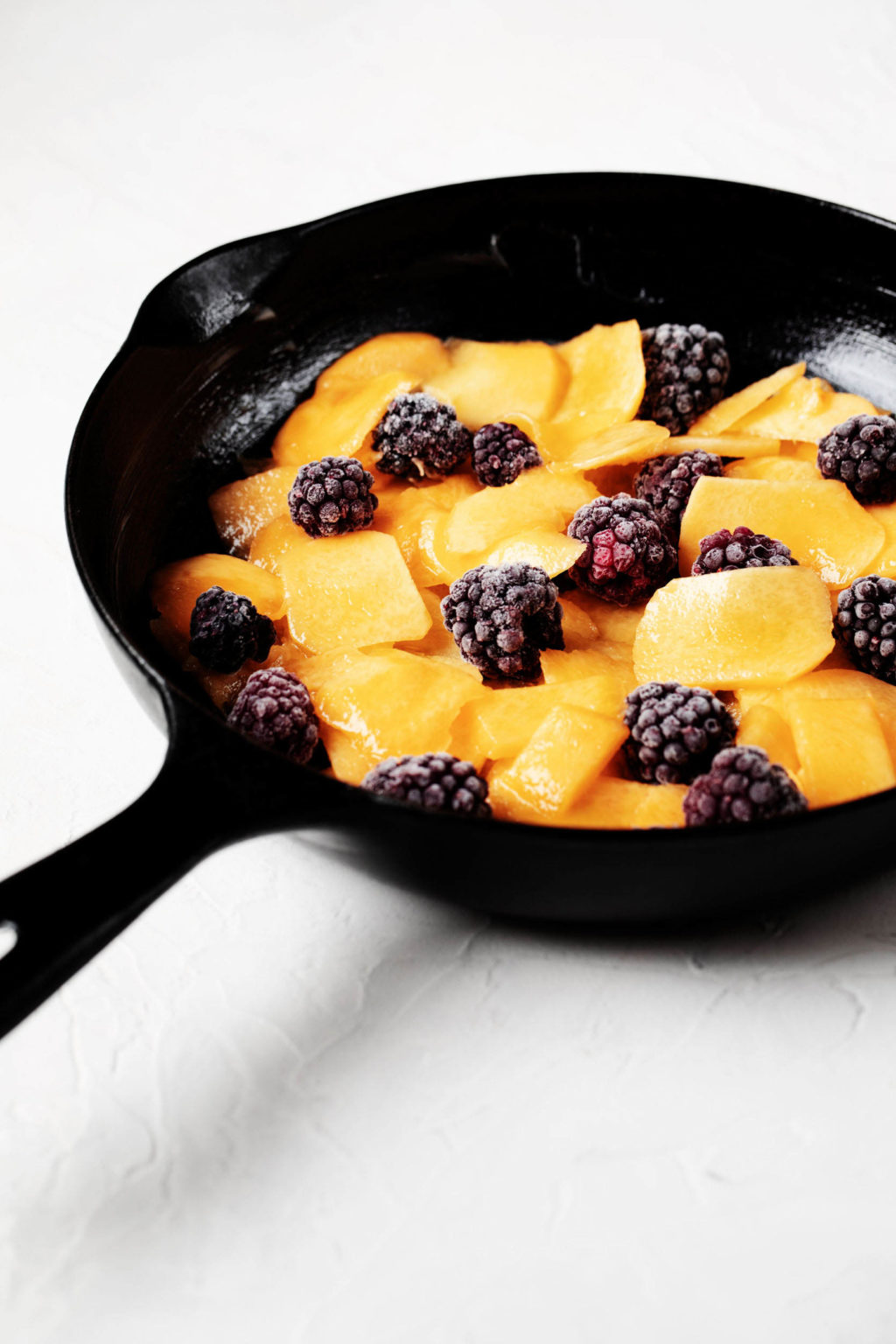 A black, cast iron skillet has been filled with peaches and blackberries. It rests on a white surface.