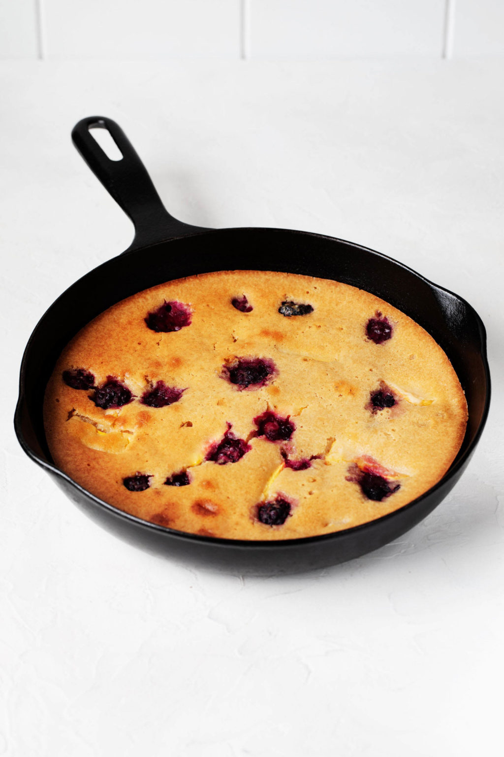 A black, cast iron skillet is filled with a vegan peach blackberry cake.