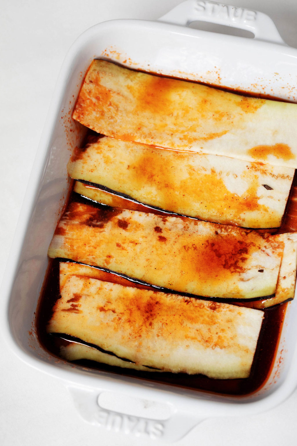 Very thin slices of eggplant are in a baking dish. They're being marinated in an orange, brothy liquid.