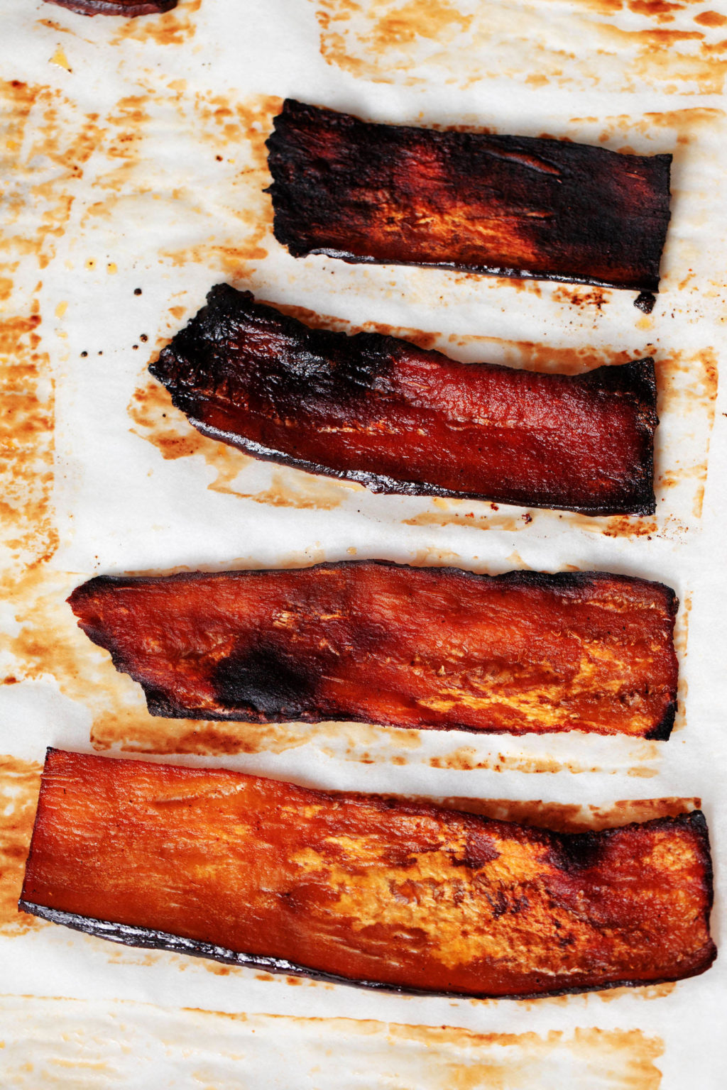 Very thin slices of vegan eggplant bacon are laid out on a parchment lined baking sheet.