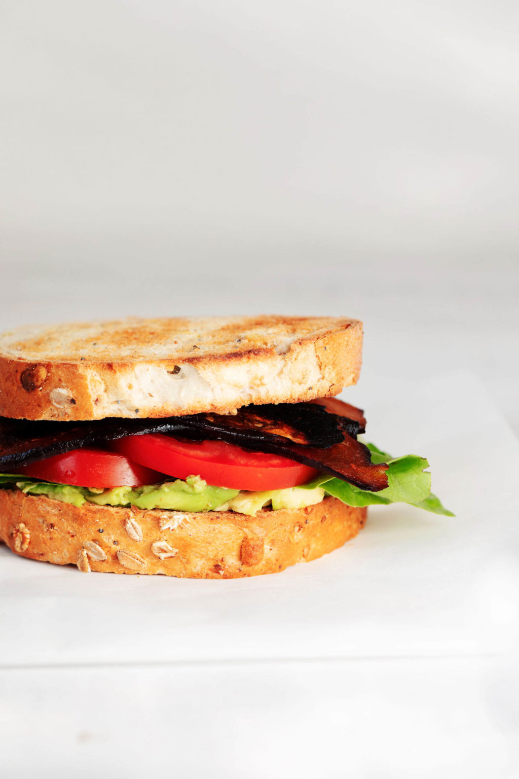 A BLT sandwich is resting on a white surface, against a gray and white background.