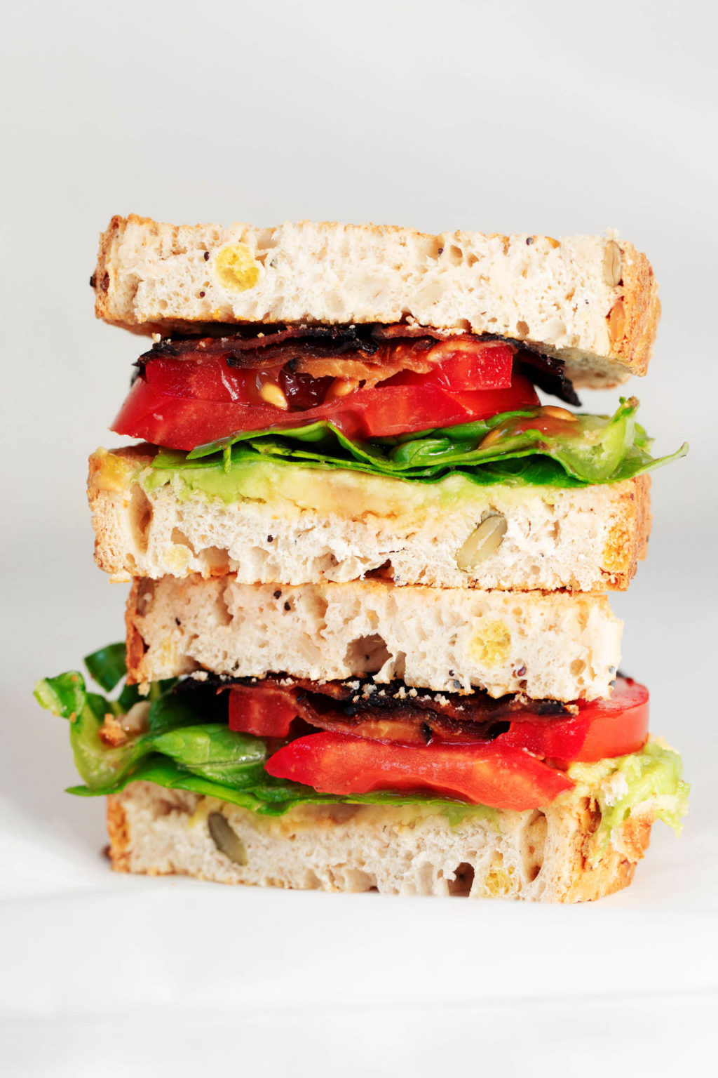 A crosswise section of a stacked, vegan BLT sandwich.