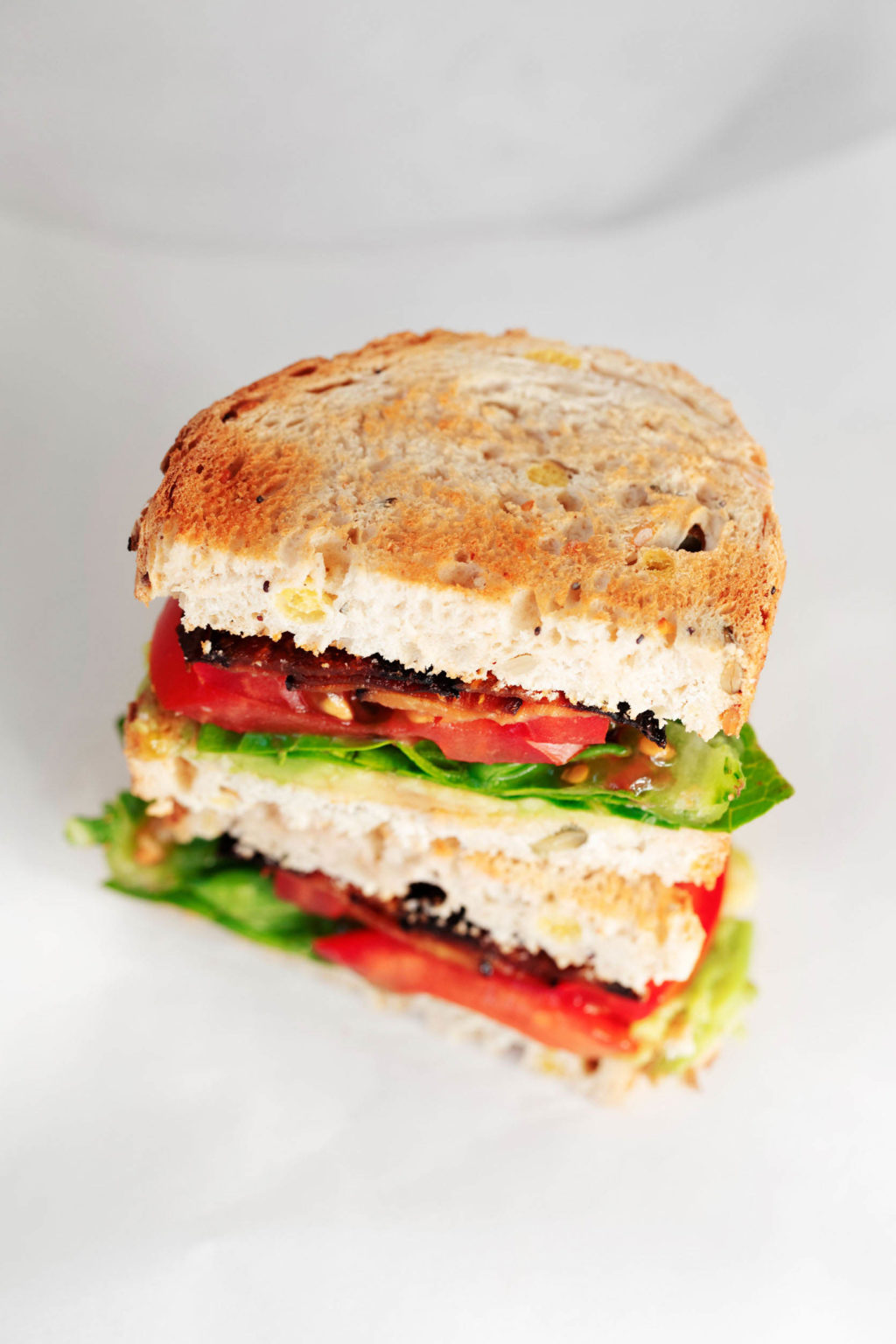 An angled, overhead image of a plant-based sandwich on white bread, with lettuce, tomato, and marinated eggplant slices.
