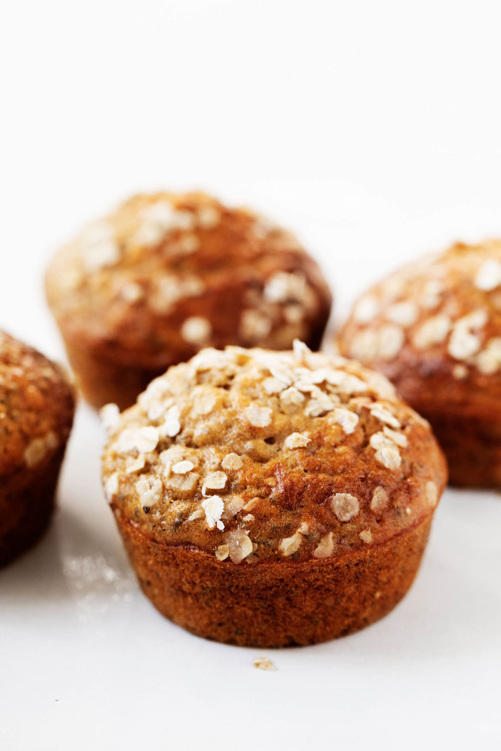An angled photograph of freshly baked banana oat chia muffins, sprinkled with fresh rolled oats.