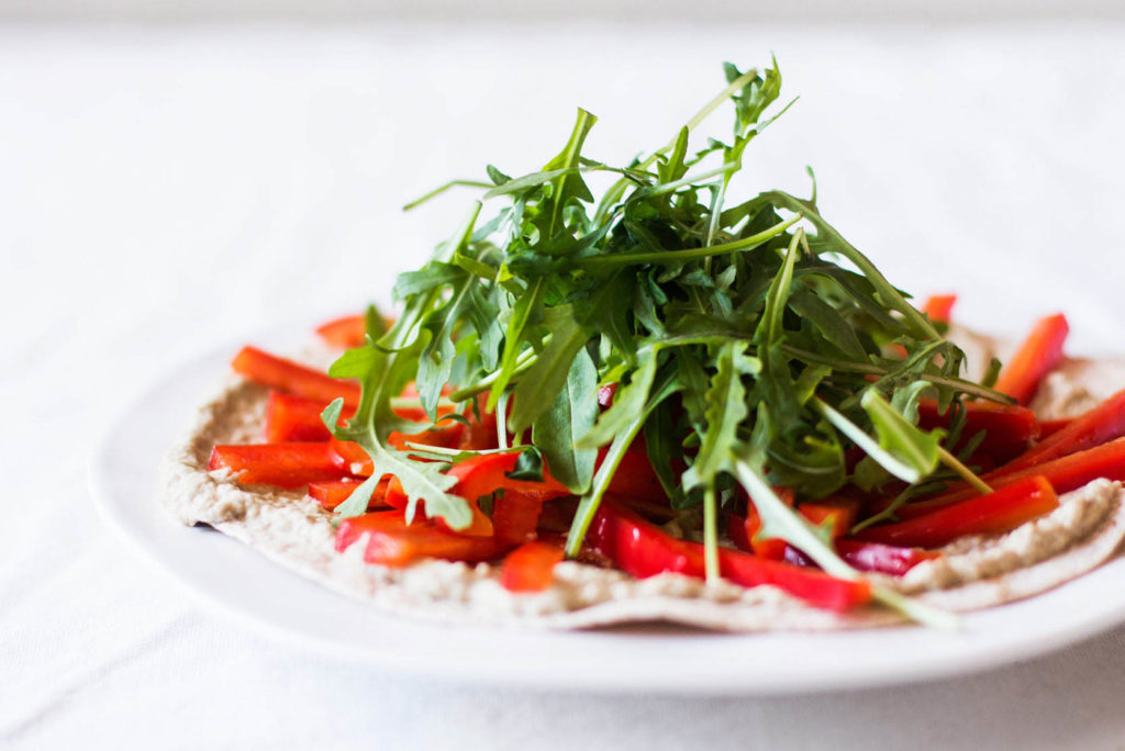 An angled photo of a plant-based flatbread, topped with a creamy spread, bell pepper, and greens.