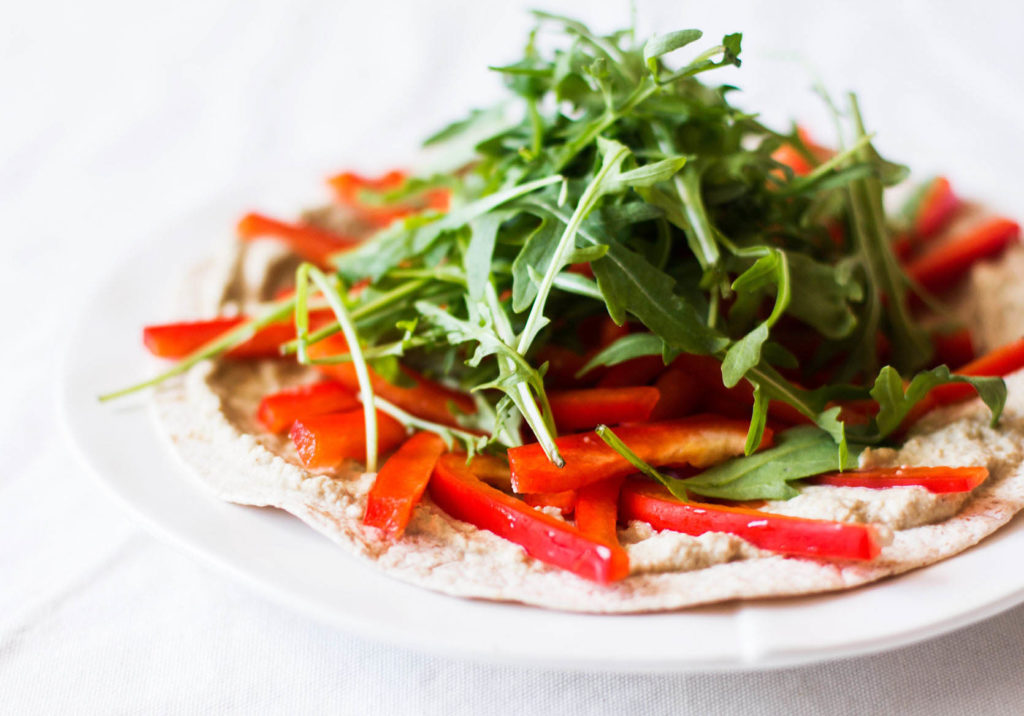 An angled photo of a tortilla pizza, which is covered in arugula and peppers.
