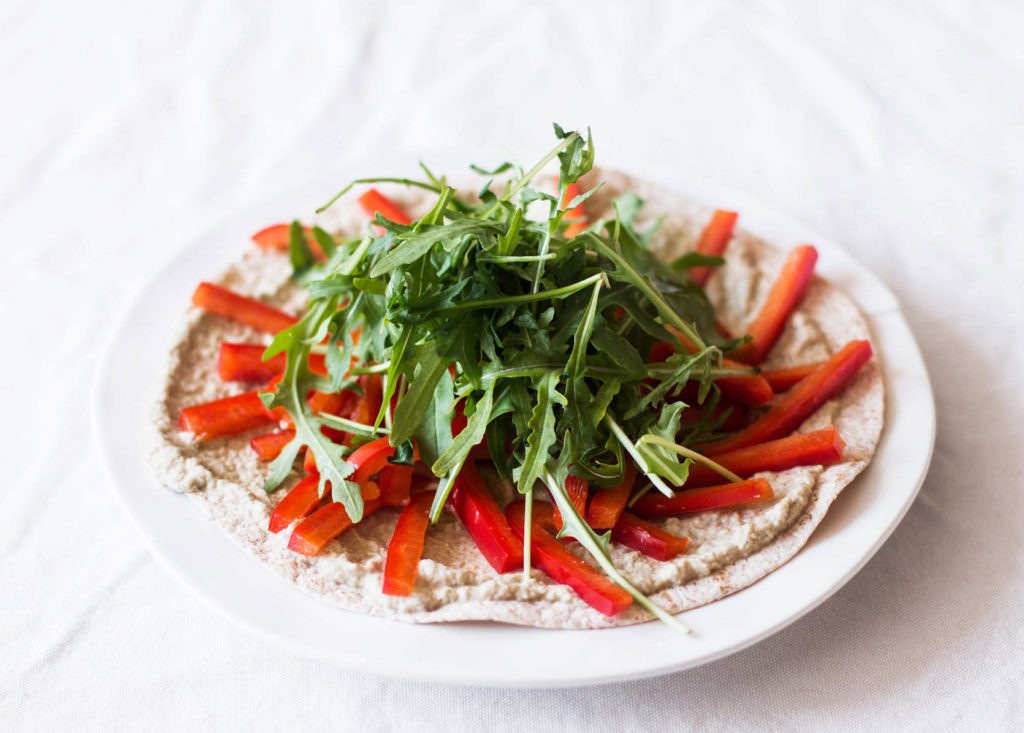 A vegan eggplant tortilla pizza has been laid out on a white tablecloth. It's topped with arugula and bell pepper strips.
