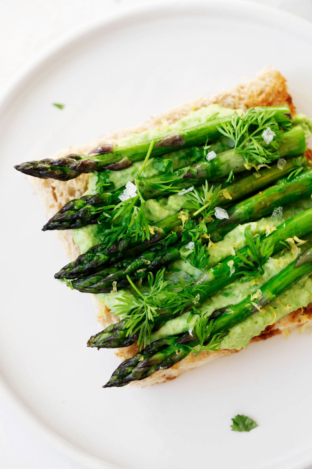 Asparagus spears have been grilled and piled onto toast with a creamy topping. They're garnished with dill, lemon zest, and flaky salt.