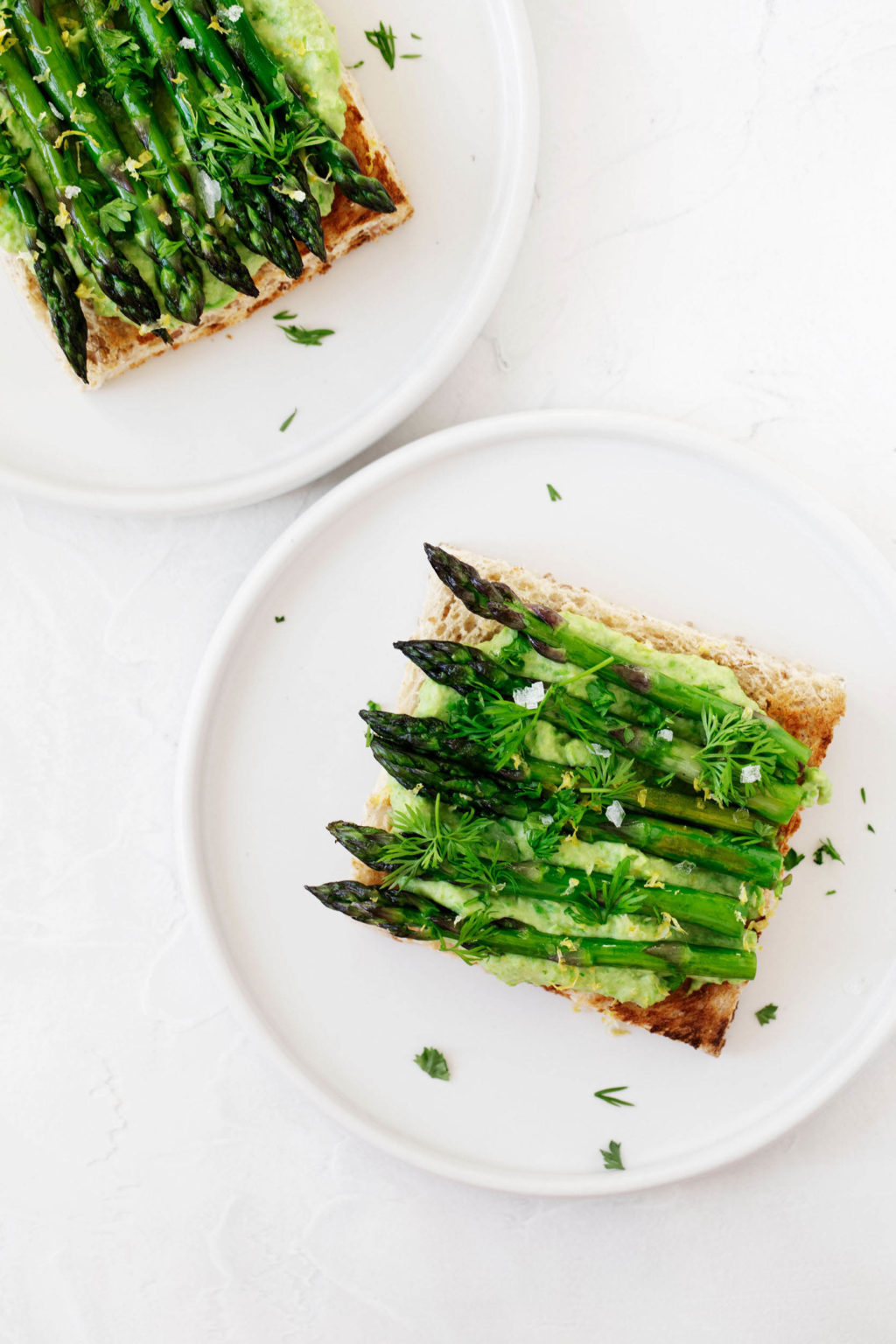 Two round, white plates are laid out on a white surface. They're being used to serve toast with a creamy pea spread and grilled asparagus spears.