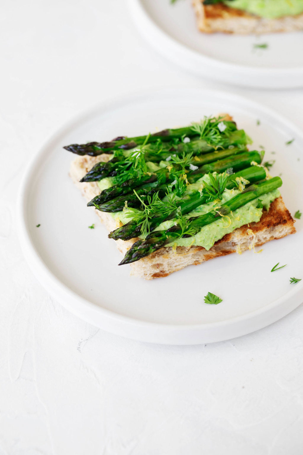 An angled photograph of a tartine made with green pea hummus and grilled asparagus spears. It rests on a white plate and white surface.