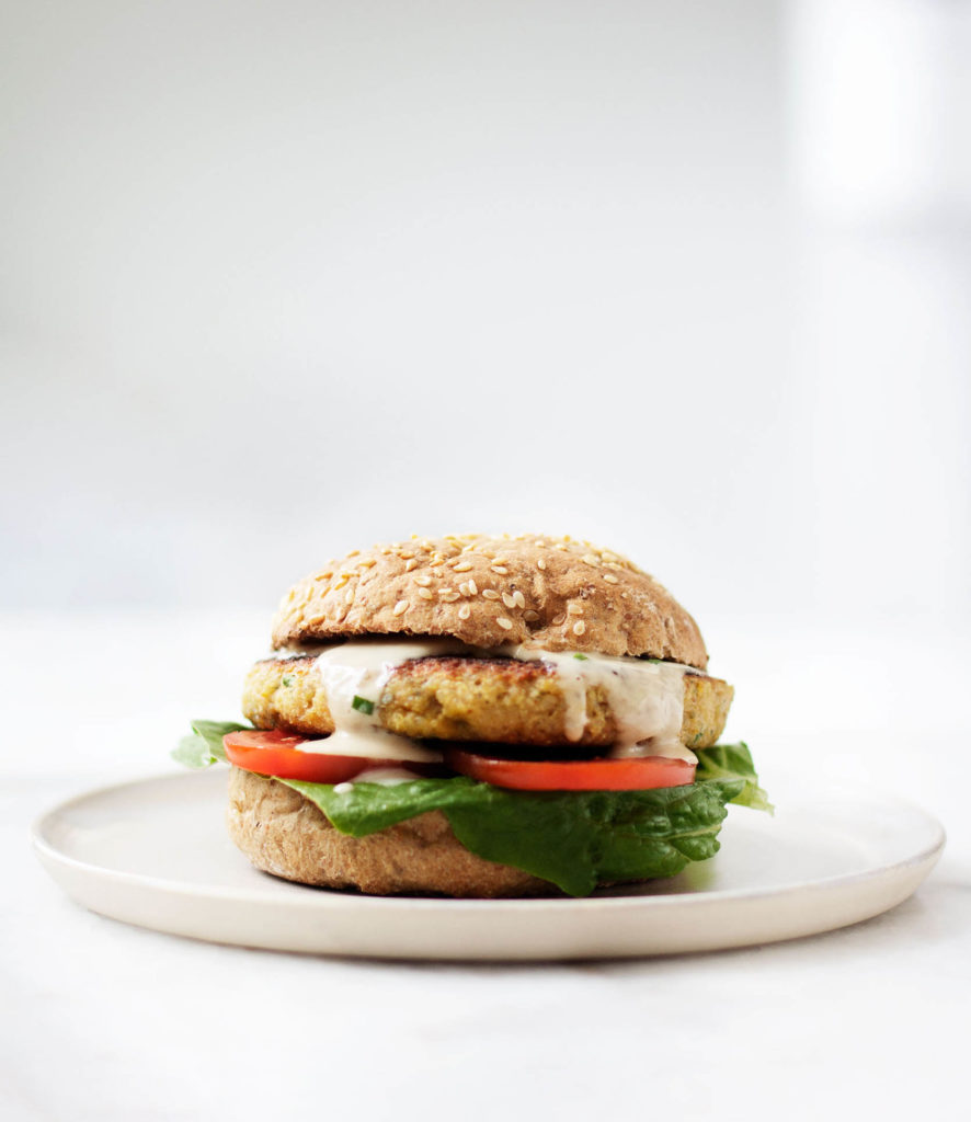 A sideways shot of a quinoa chickpea burger, served on a bun with lettuce, tomato, and tahini sauce.
