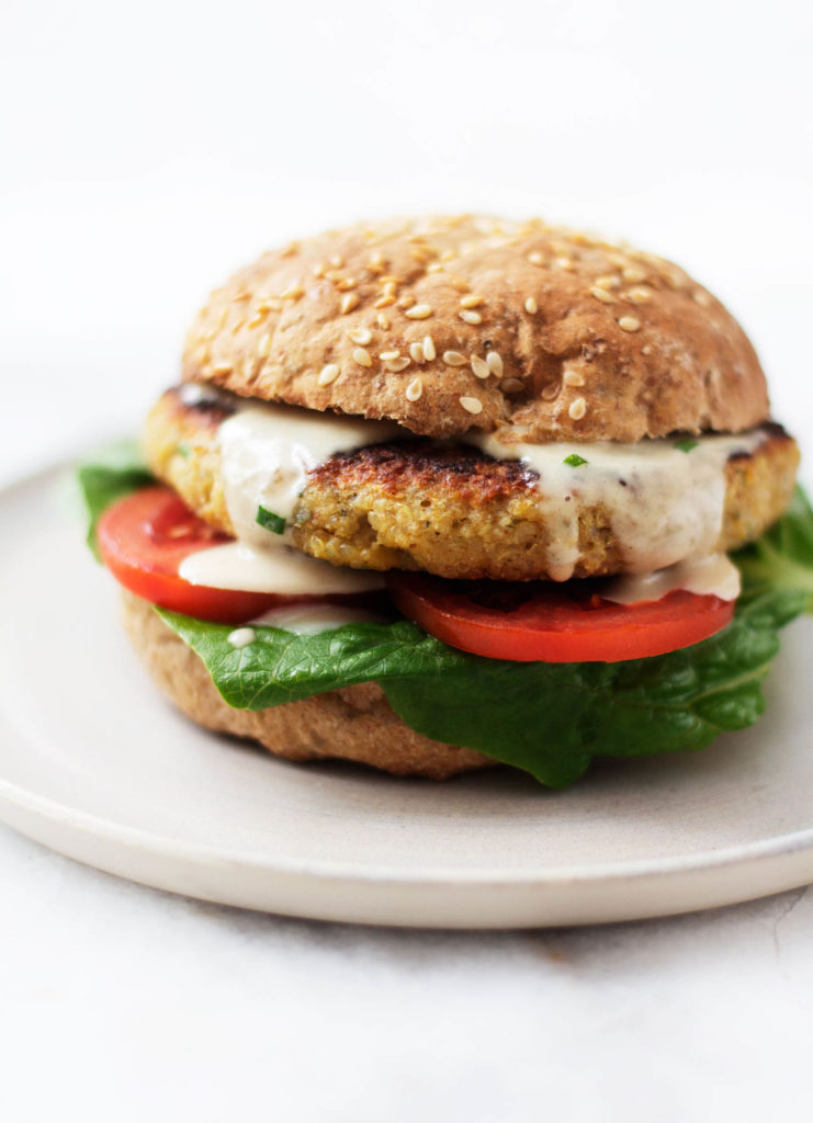 A close up of a vegan quinoa chickpea za'atar burger, covered in sauce and sitting on crisp vegetables.