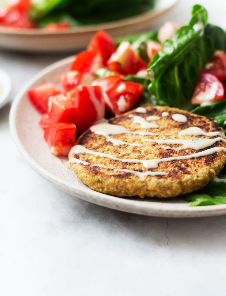 A side angled photograph of a quinoa chickpea zaatar burger patty, served with lettuce wraps and tahini dressing.