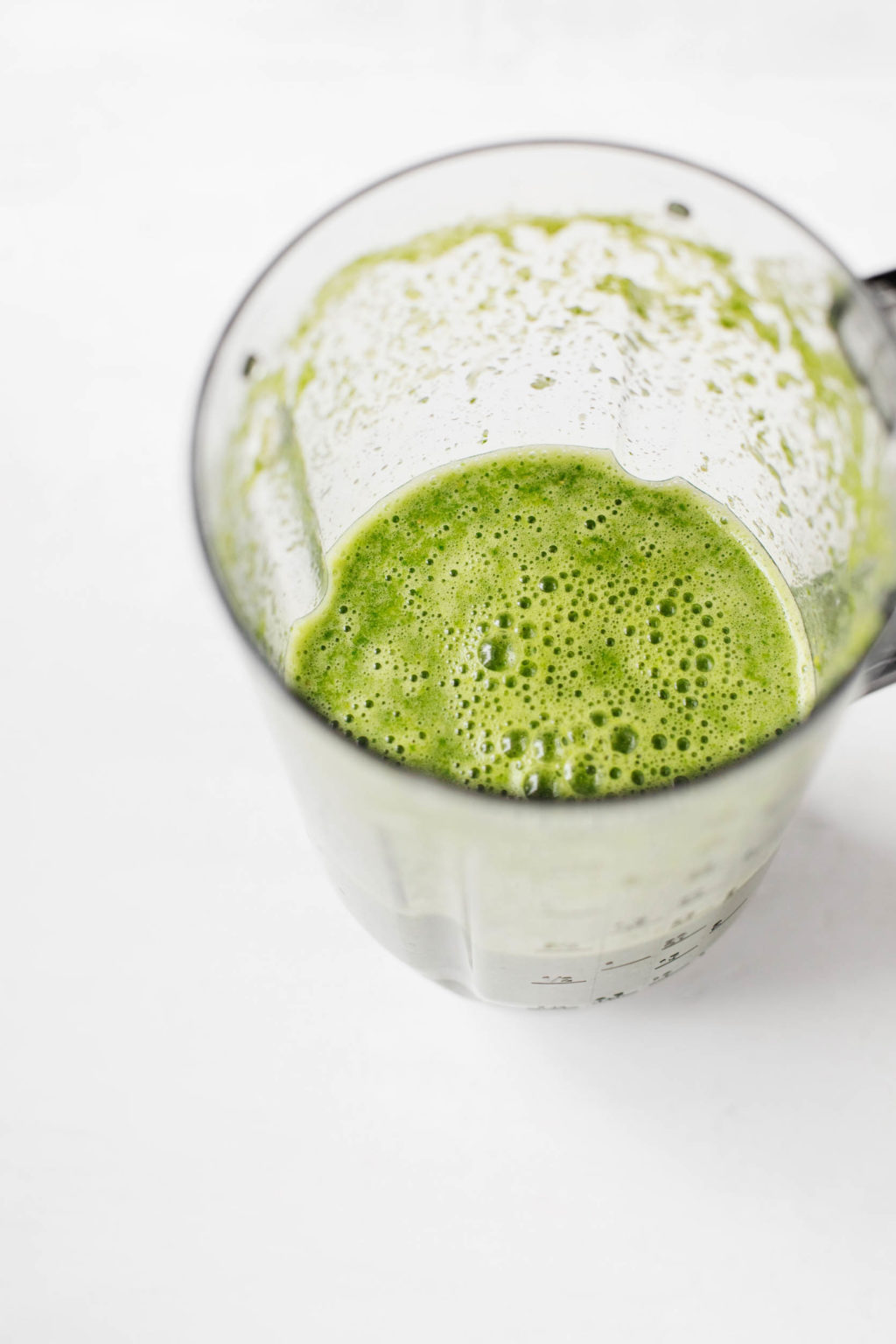 A liquid measuring cup has been filled with a frothy, freshly made, easy green juice.