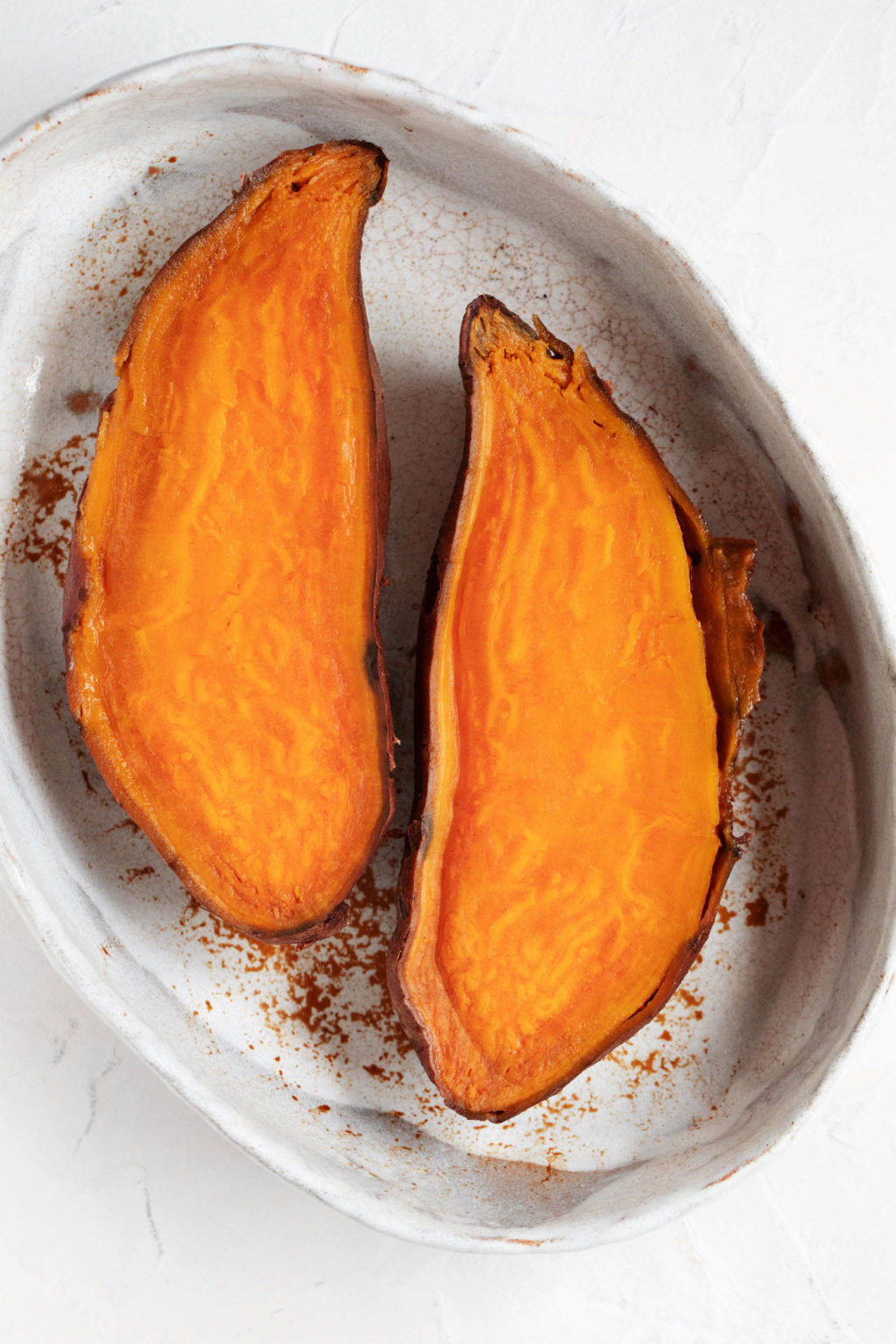 A ceramic baking dish holds two, recently baked sweet potato halves.