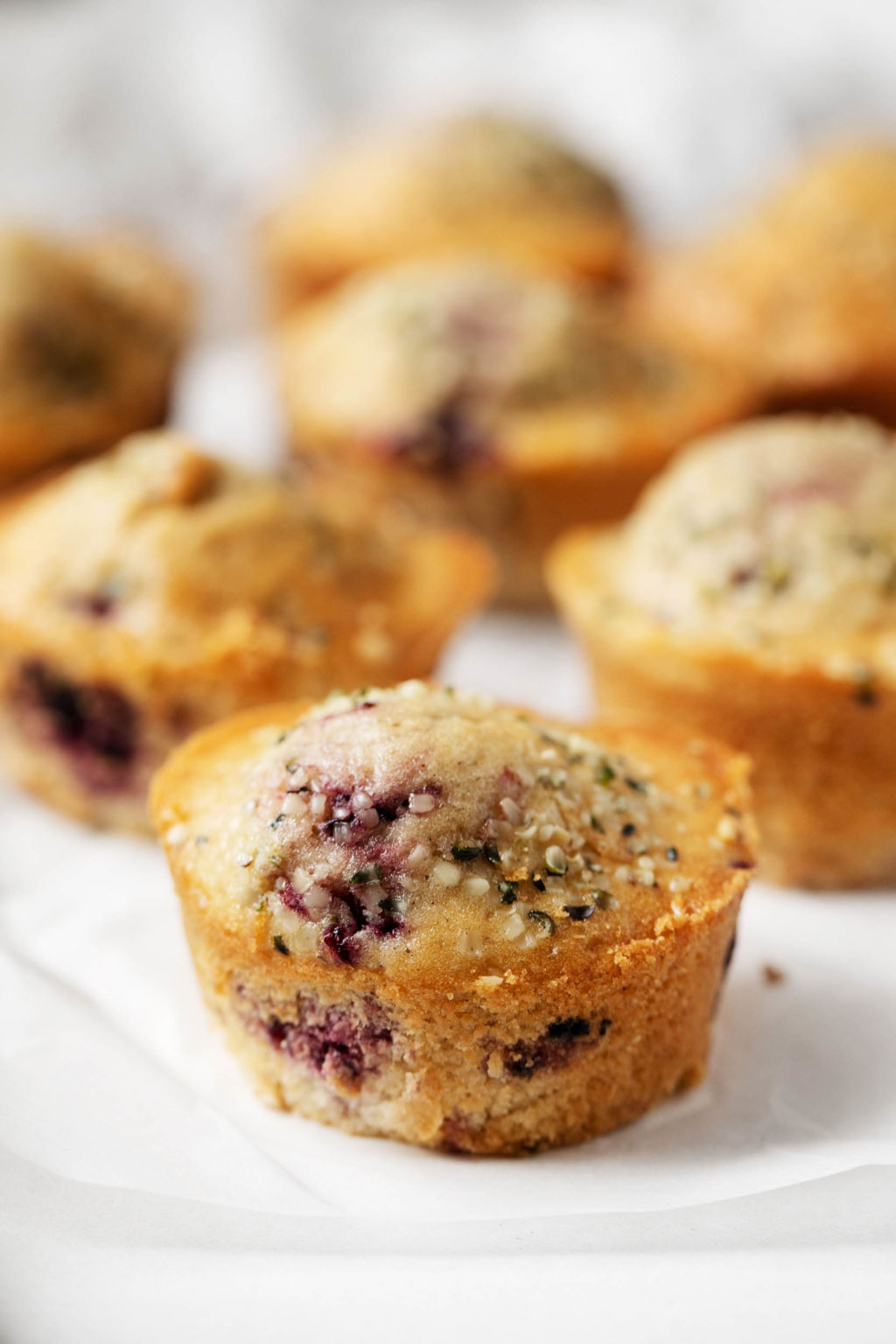 A close up photograph of a freshly baked vegan berry spelt muffin, topped with nutritious hemp seeds.
