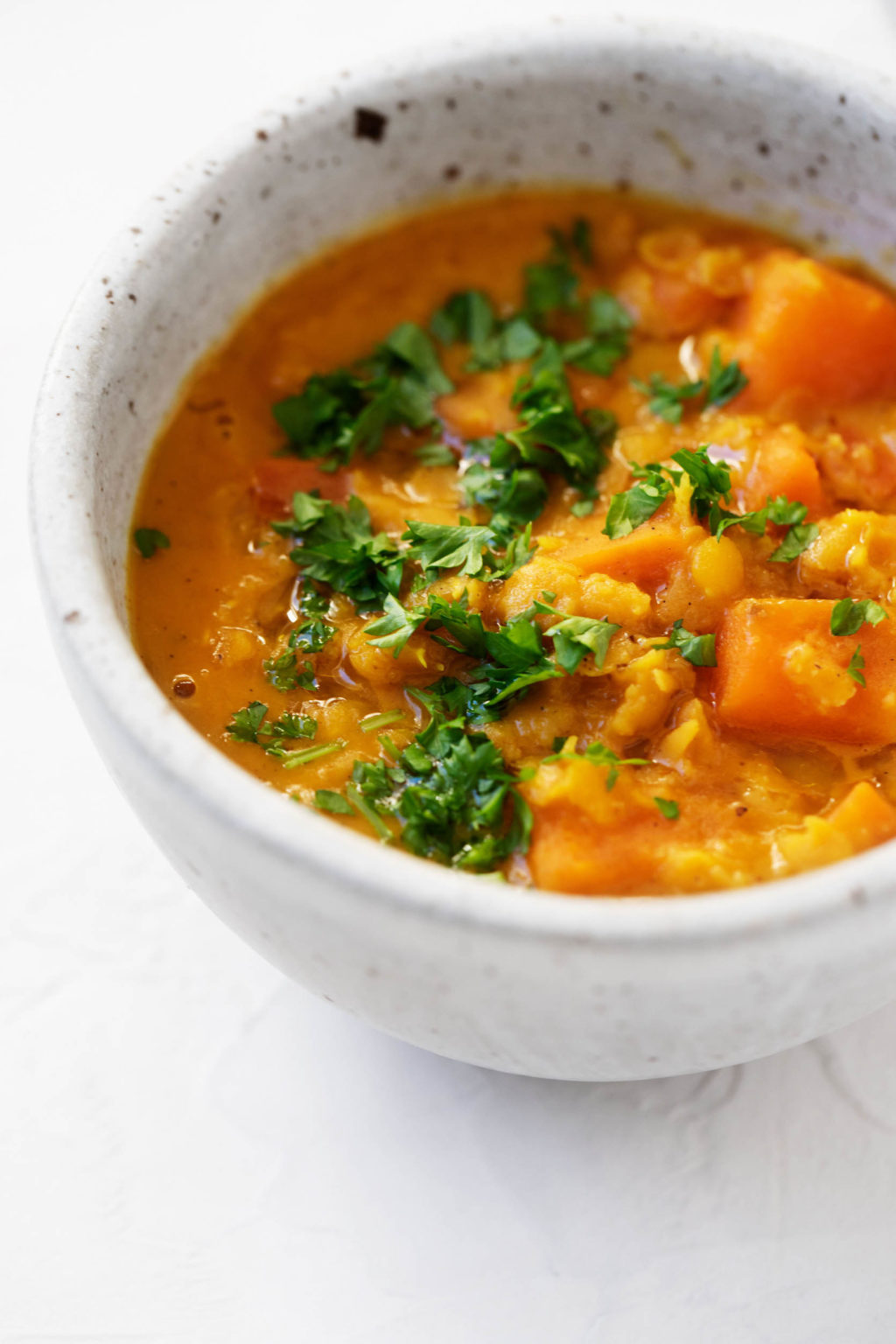 A close up photograph of curried sweet potato lentils in a small bowl, topped with chopped herbs.