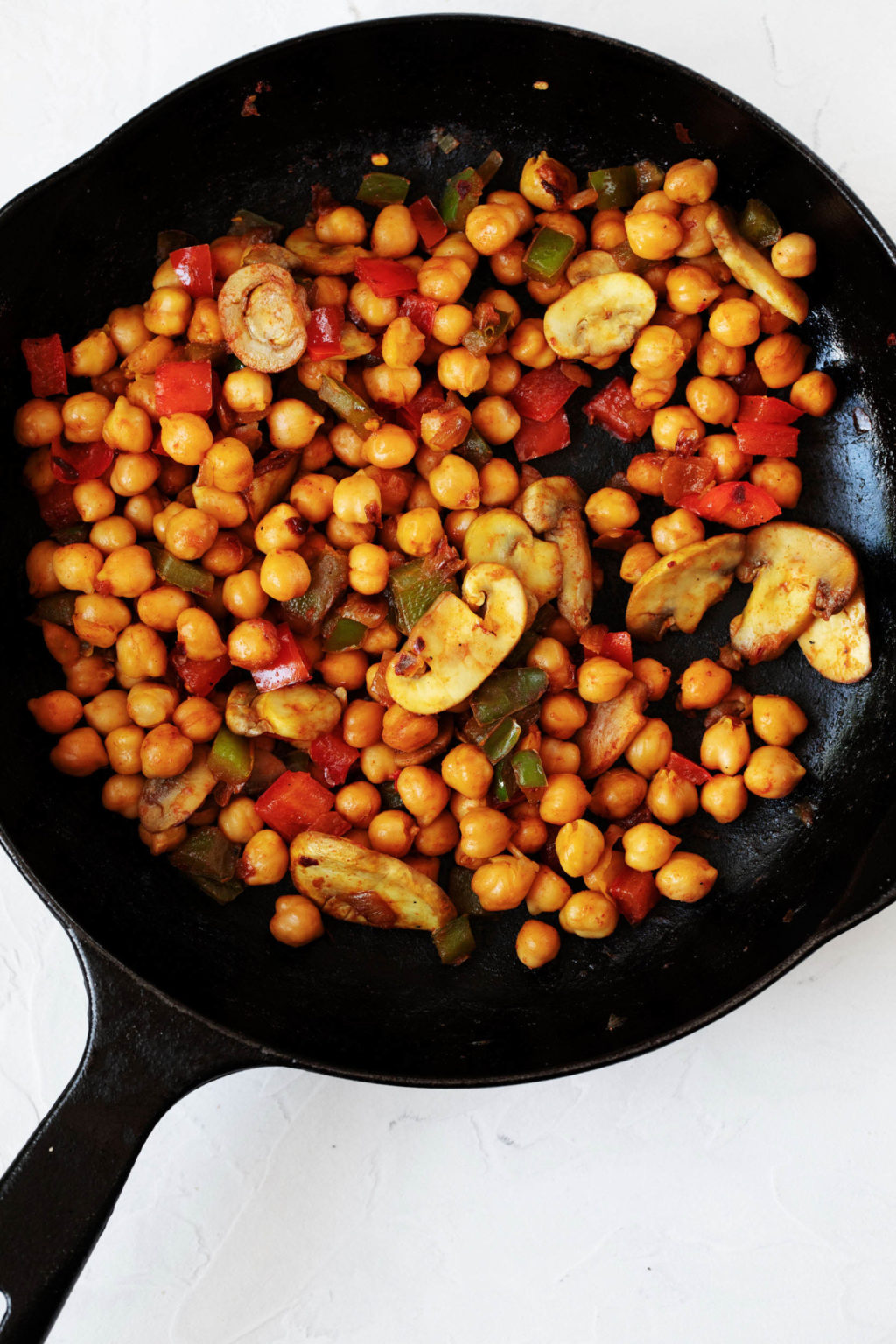 A black, cast iron skillet holds a mixture of sautéed vegetables and garbanzo beans.