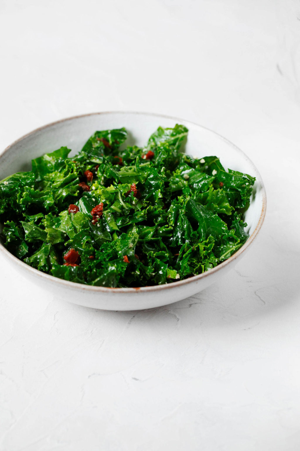 An angled photograph of a bed of dark, leafy greens, which are specked with small pieces of sun-dried tomato. They're sitting in a ceramic bowl.
