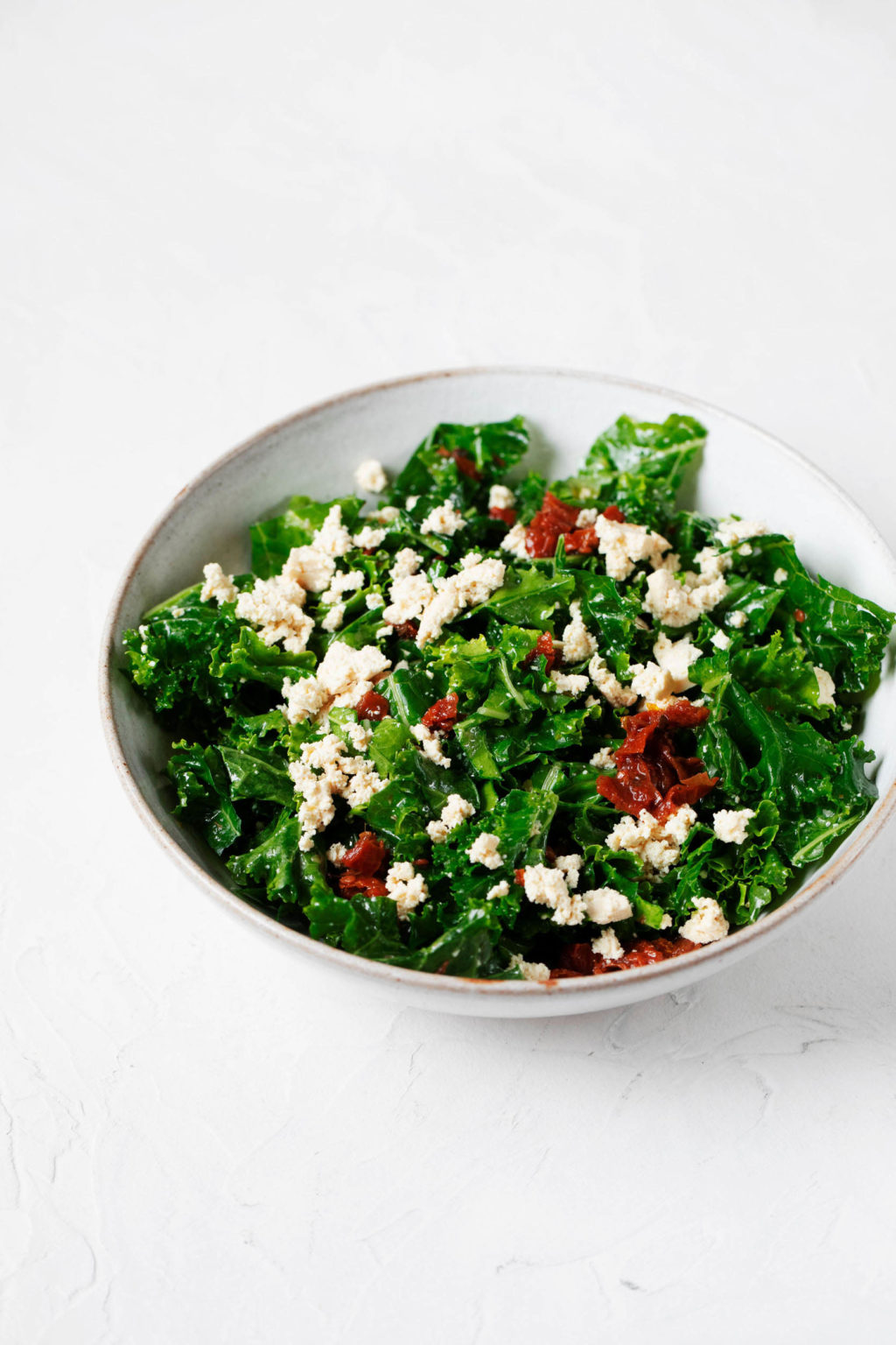 A white, ceramic bowl holds a tofu feta kale salad, which is prepared with small pieces of red sun-dried tomatoes.
