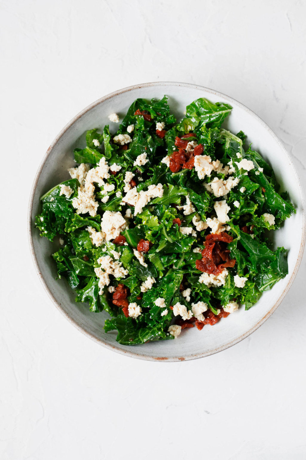 An overhead image of a kale-based, summery salad with added tofu. The salad is in a white serving bowl.