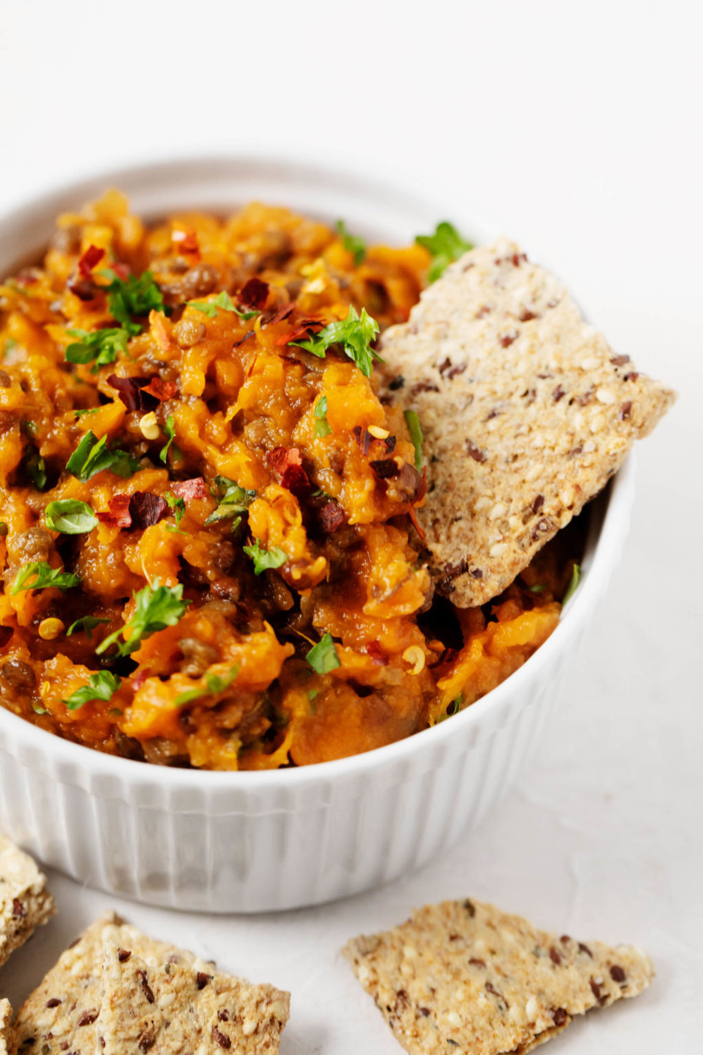 A white ramekin has been filled with a vegan spread made with sweet potatoes and lentils. A single, whole grain cracker is being dunked into the spread.