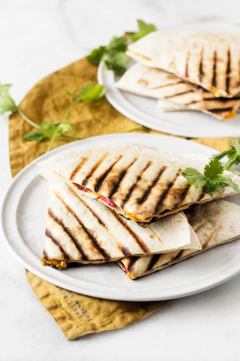 A stack of quesadillas has been prepared with plant-based ingredients. It's resting on a white plate and rust colored napkin.