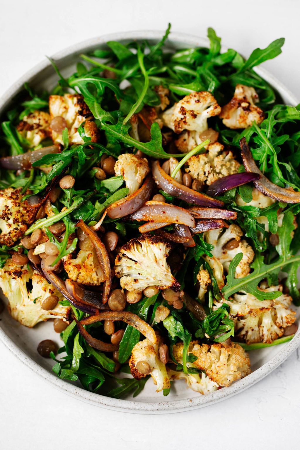 A zoomed in, birds eye photograph of a za'atar roasted cauliflower salad, which rests on a white ceramic plate.