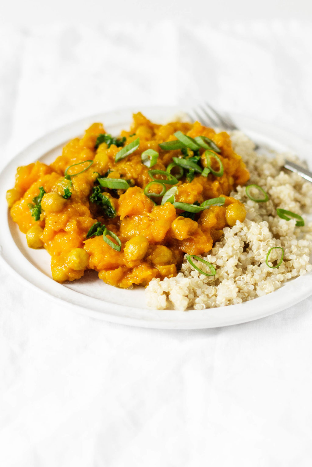Golden butternut chickpea curry is a fast and flavorful meal—especially when it's served with freshly cooked couscous and chopped green onions.