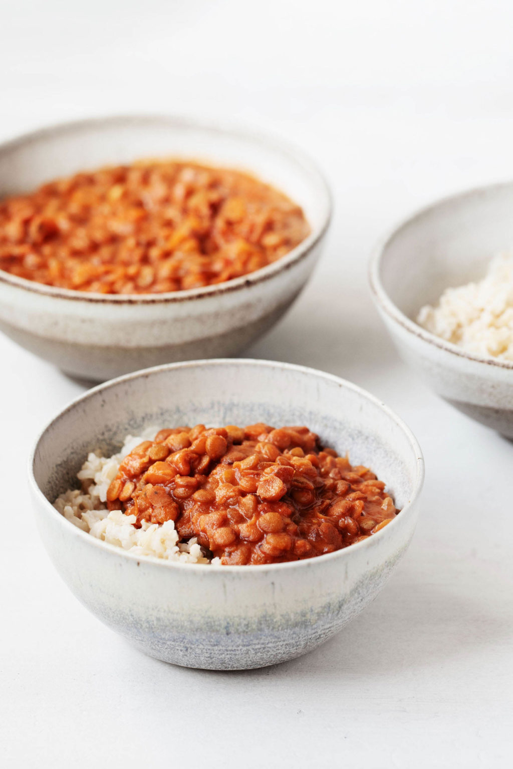 Two ceramic bowls have been piled with masala spiced, cooked lentils. Another bowl in the backdrop is filled with cooked brown rice.