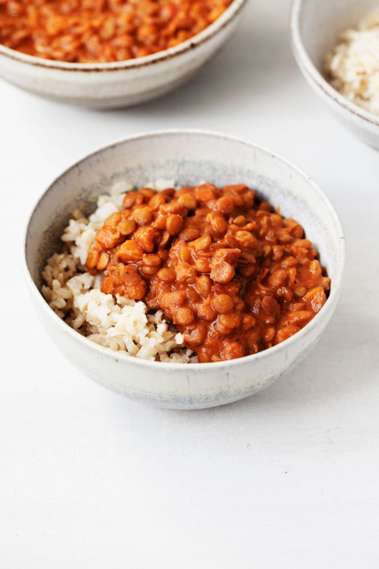 Two white, ceramic bowls hold dishes of masala spiced lentils and cooked brown rice.