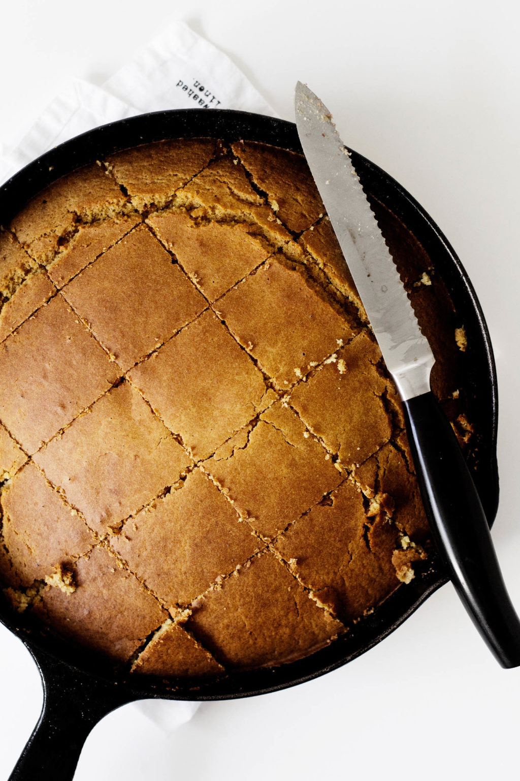 A skillet full of warm cornbread. The cornbread has been cut into squares, ready for eating.