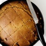 Vegan pumpkin cornbread has been cut into warm squares just after baking.