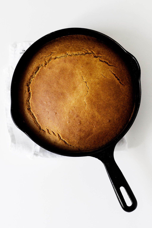 A skillet holding freshly baked, vegan pumpkin cornbread.