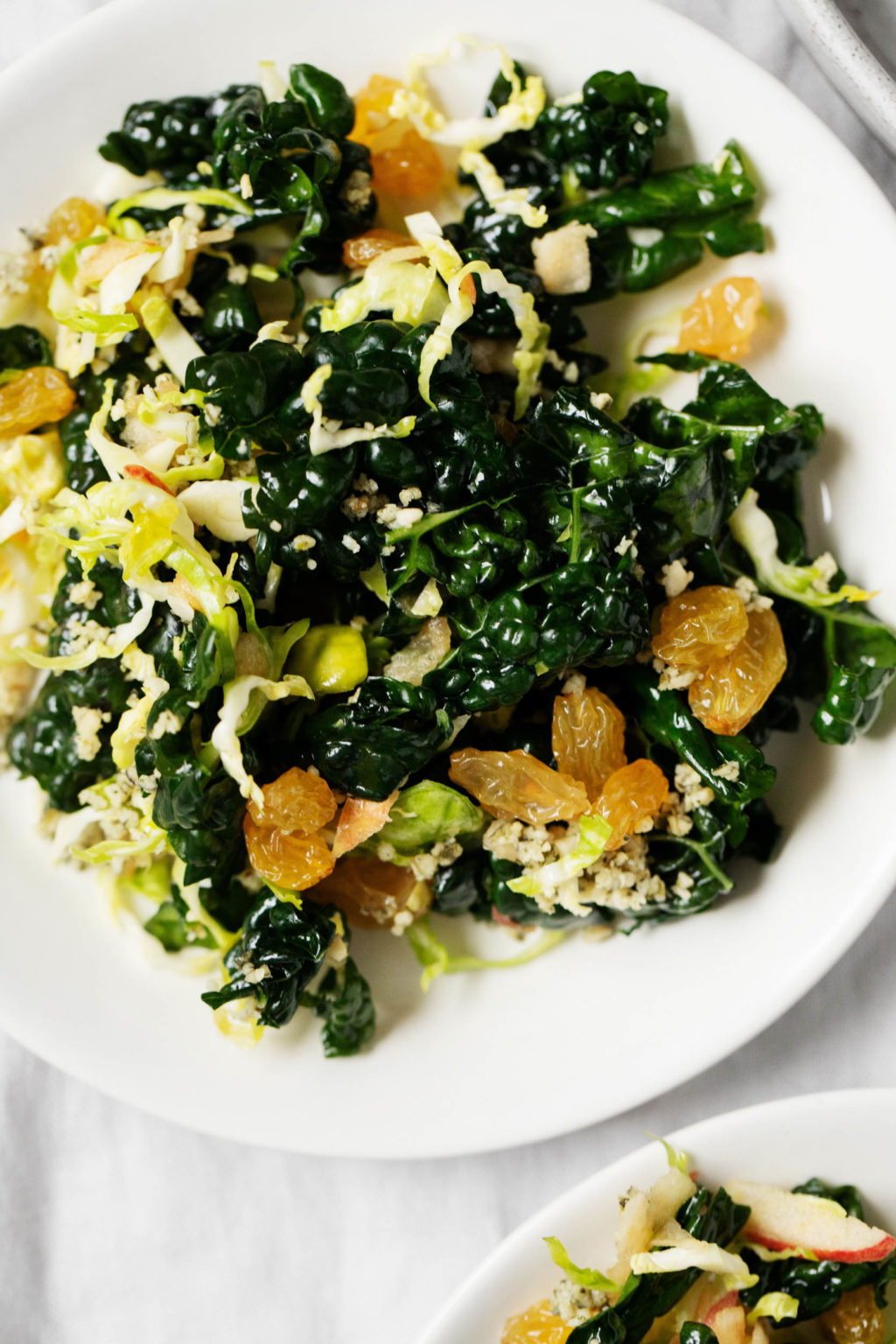 A zoomed in photograph of a serving plate, which is topped with a Brussels sprout kale salad.